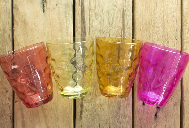 Vidrios multicolores del agua, que se coloca en un tabl de madera imagenes de archivo