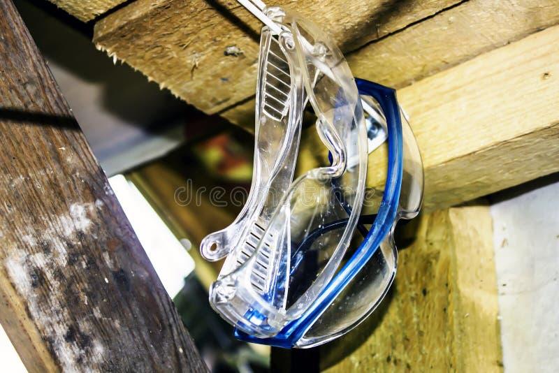 Vidrios plásticos de la protección ocular que cuelgan en el garaje Los vidrios son utilizados durante la siega de la hierba por u foto de archivo libre de regalías