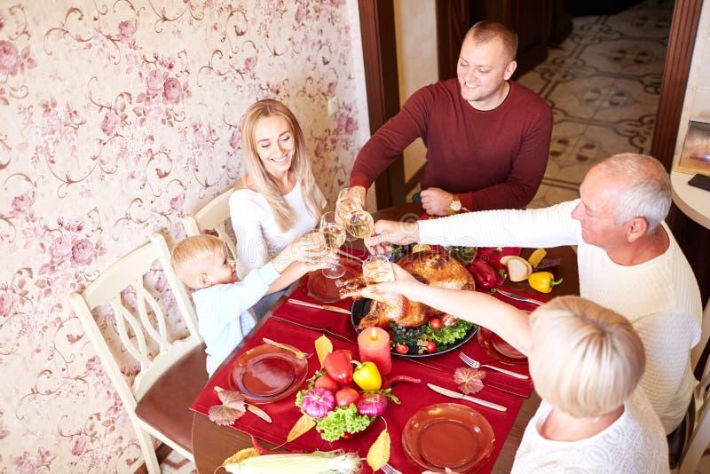 Vidrios que animan de la familia hermosa en acción de gracias en un fondo borroso Concepto de celebración feliz imagen de archivo libre de regalías
