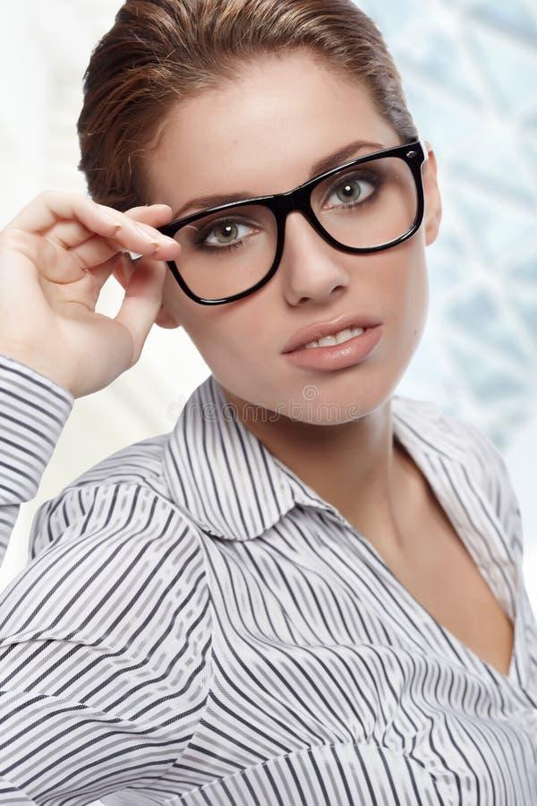 Vidrios que desgastan de la mujer en oficina foto de archivo libre de regalías
