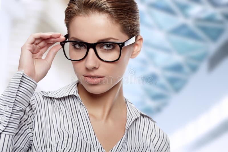 Vidrios que desgastan de la mujer en oficina fotos de archivo libres de regalías