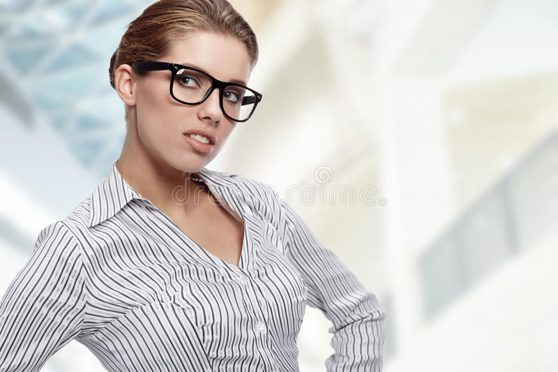 Vidrios que desgastan de la mujer en oficina fotografía de archivo