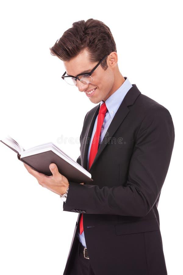 Vidrios que desgastan del hombre de negocios y lectura de un libro fotos de archivo