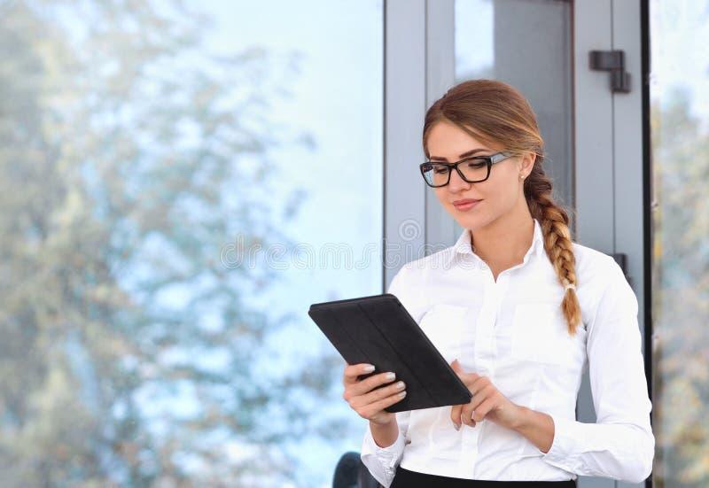 Vidrios que llevan atractivos de la mujer joven que leen su tableta de la pantalla táctil imágenes de archivo libres de regalías