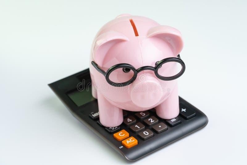 Vidrios que llevan de la hucha rosada en la calculadora negra en el fondo blanco usando como cálculo del presupuesto, del coste o imágenes de archivo libres de regalías