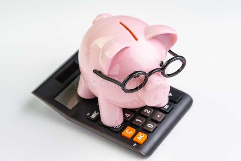 Vidrios que llevan de la hucha rosada en la calculadora negra en el fondo blanco usando como presupuesto de educación, coste o cá foto de archivo