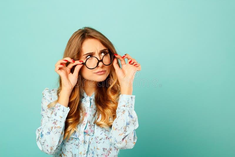 Vidrios que llevan de la muchacha bastante pensativa sobre fondo azul imagen de archivo libre de regalías