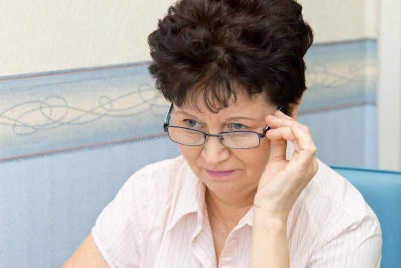 Vidrios que llevan de la mujer mayor positiva agradable en casa fotos de archivo