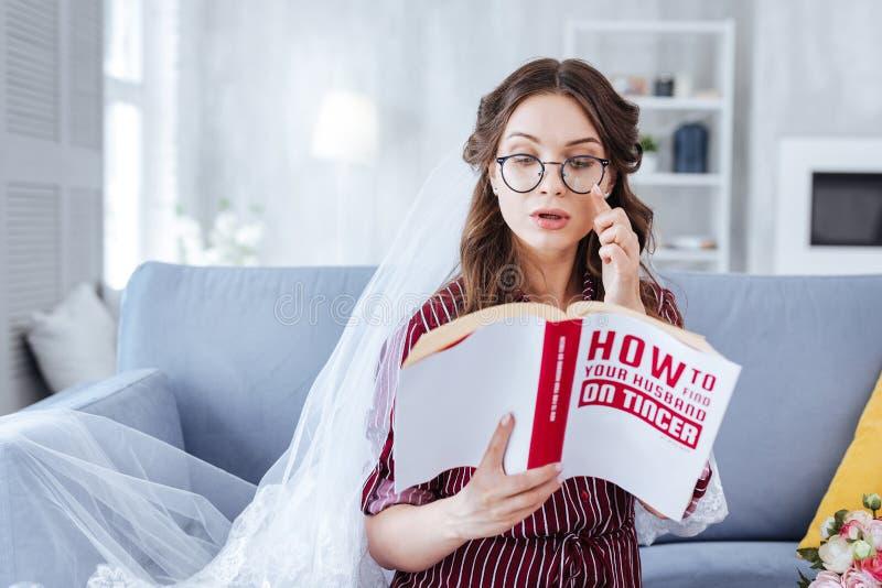 Vidrios que llevan de la novia joven que leen la literatura imagen de archivo