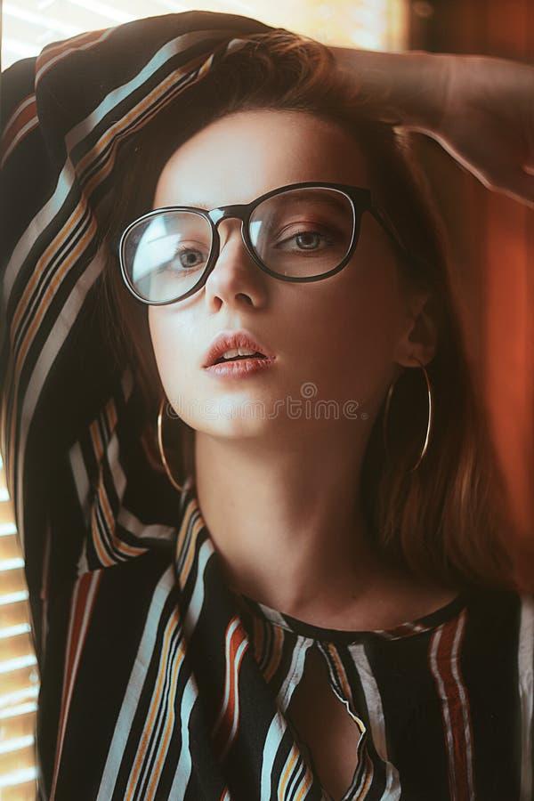 Vidrios que llevan de moda de la belleza del modelo del retrato atractivo de la mujer Mujer elegante que mira la cámara en los vi imagen de archivo