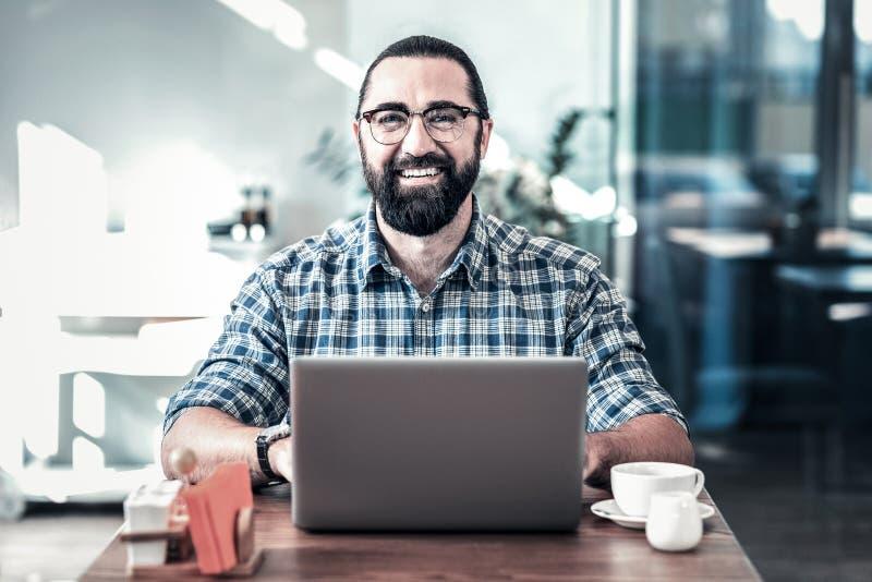 Vidrios que llevan del hombre barbudo alegre que sonríen después de día acertado foto de archivo libre de regalías