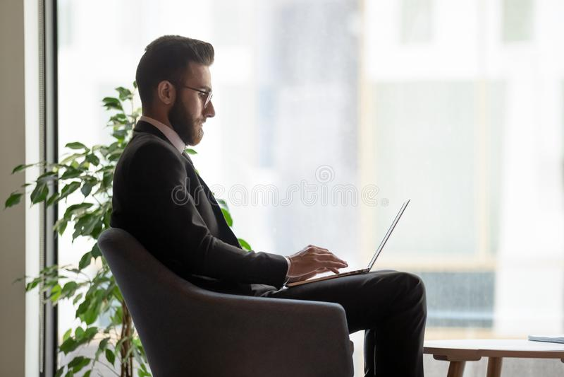 Vidrios que llevan del hombre de negocios serio usando el ordenador portátil cerca de la ventana grande imagen de archivo
