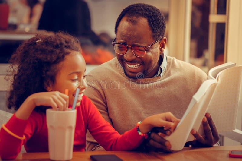 Vidrios que llevan del padre que sienten el libro de lectura memorable para la hija imágenes de archivo libres de regalías