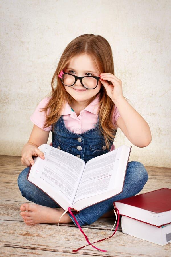Vidrios que llevan del pequeño empollón joven y lectura de un libro fotos de archivo libres de regalías