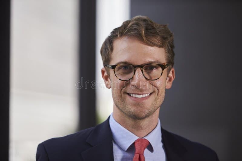 Vidrios que llevan que sonríen, ascendente cercano del hombre de negocios blanco joven fotos de archivo libres de regalías