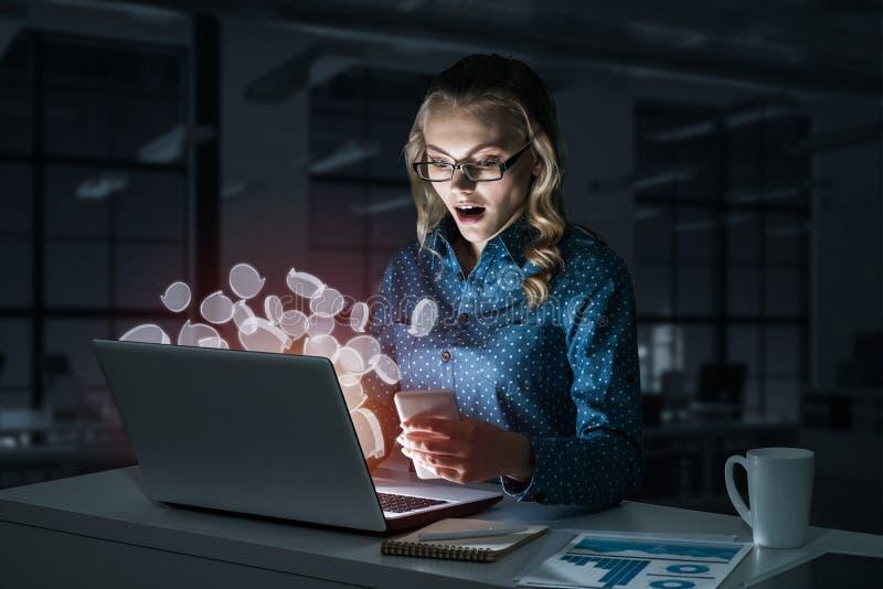 Vidrios que llevan rubios atractivos en oficina oscura usando el ordenador portátil M foto de archivo libre de regalías