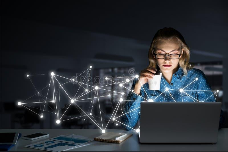Vidrios que llevan rubios atractivos en oficina oscura usando el ordenador portátil Técnicas mixtas foto de archivo