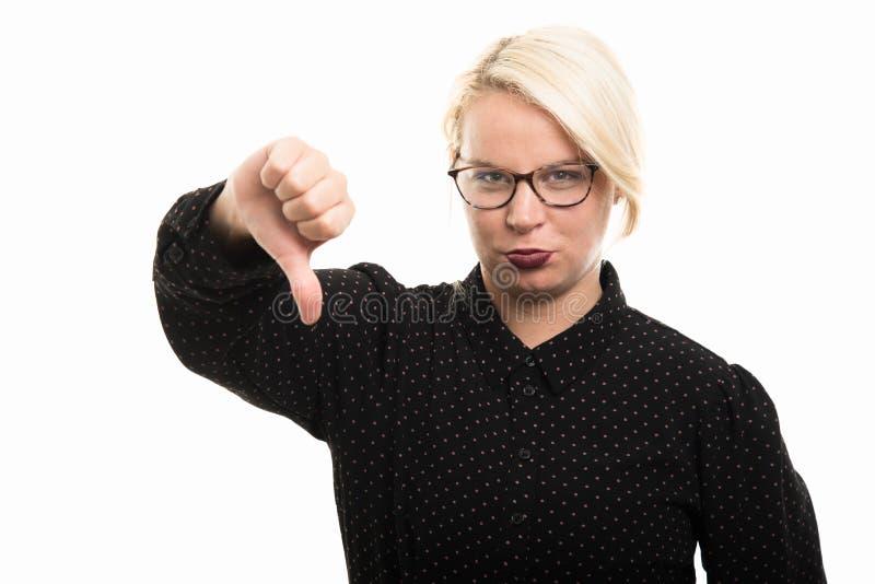 Vidrios que llevan rubios jovenes del profesor de sexo femenino que muestran el pulgar abajo g fotografía de archivo