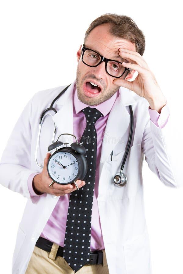 Vidrios que llevan soñolientos, agotados del doctor de sexo masculino que sostienen un despertador, cansado después de DA ocupada imagen de archivo