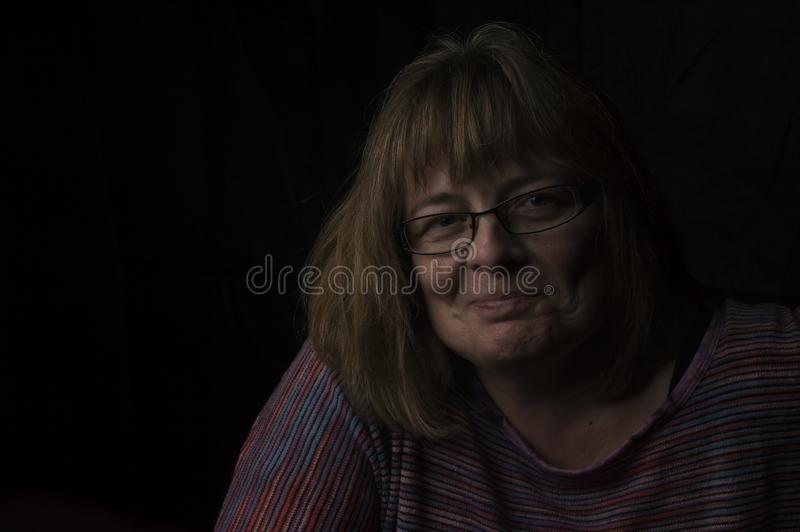 Vidrios que llevan sonrientes de la mujer madura fotos de archivo
