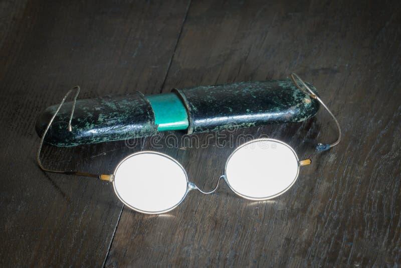 Vidrios quebrados viejos con un caso de papel en el fondo de una tabla de madera imágenes de archivo libres de regalías