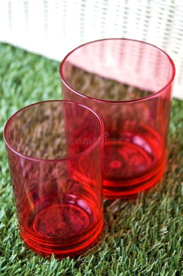 Vidrios rojos en hierba verde fotografía de archivo