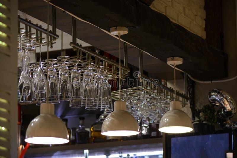 Vidrios suspendidos en una barra, vidrios para el vino y champán fotografía de archivo libre de regalías