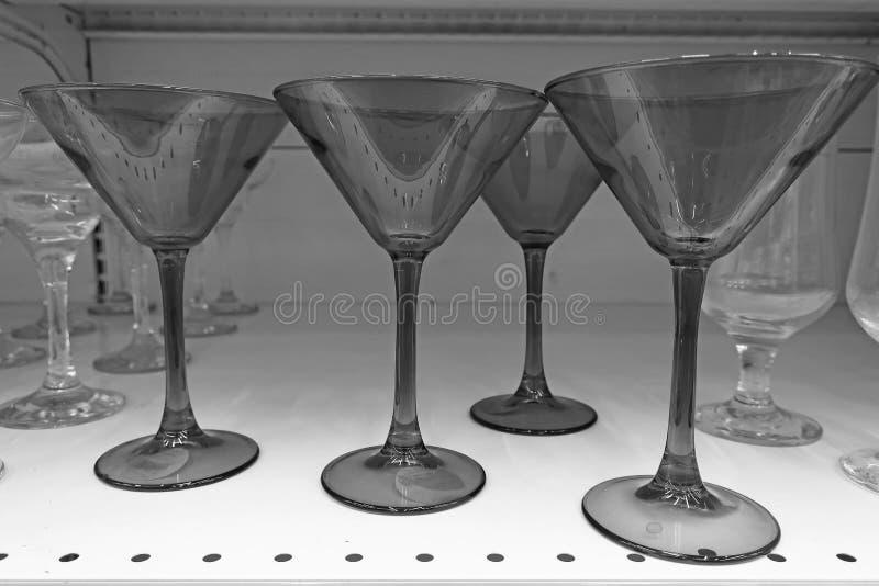Vidrios transparentes para el alcohol en el estante imagenes de archivo