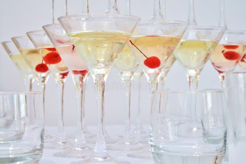 Vidrios triangulares de martini, llenados de champán con las cerezas y el nitrógeno líquido, creando el vapor, forma de una pirám fotografía de archivo