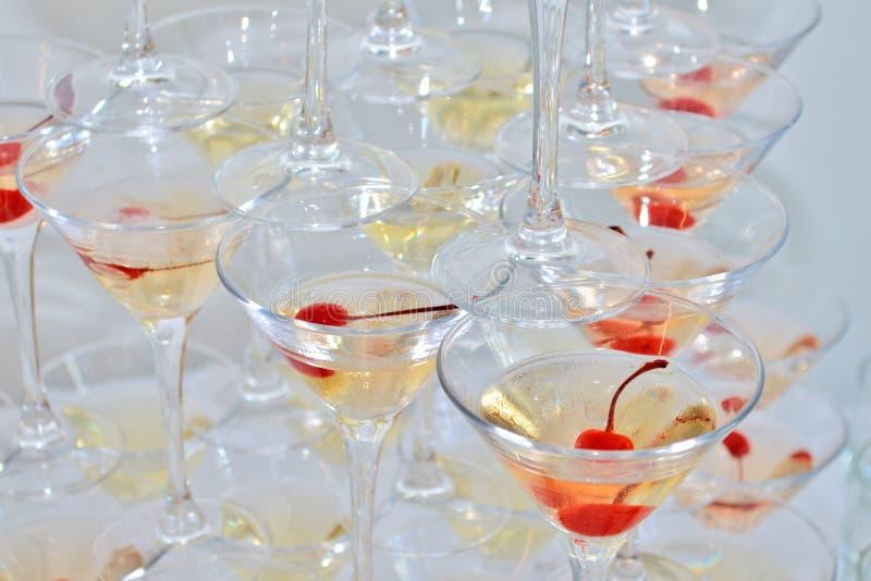 Vidrios triangulares de martini, llenados de champán con las cerezas y el nitrógeno líquido, creando el vapor, visión superior imagen de archivo