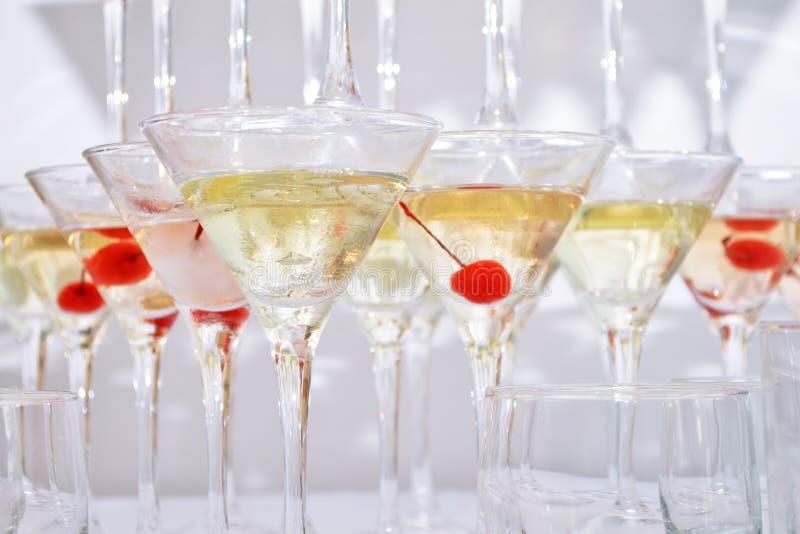 Vidrios triangulares de martini, llenados del vino con las cerezas y el nitrógeno líquido, creando el vapor, construido en pirámi foto de archivo libre de regalías