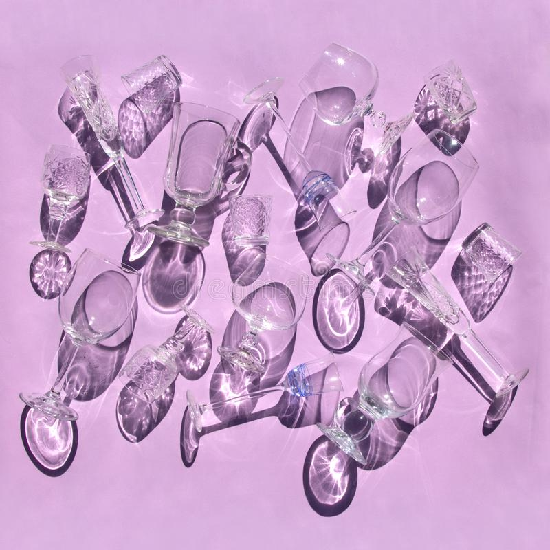 Vidrios vacíos de diversas formas para el vino, whisky, vino reflexionado sobre, vodka, mentira del licor en fondo rosado en luz  fotos de archivo