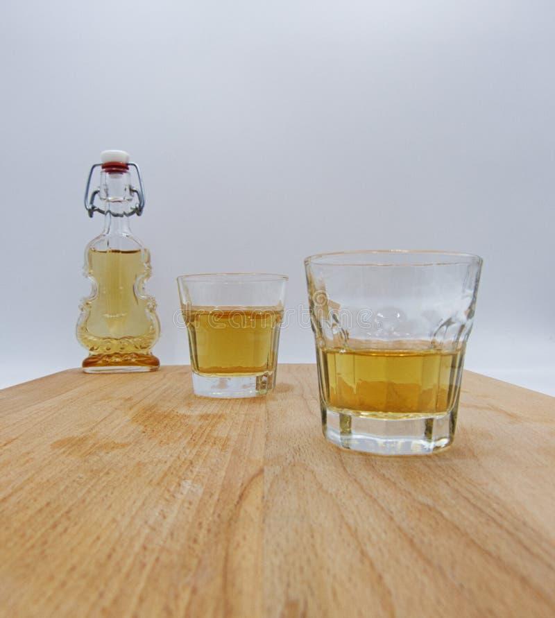 Vidrios y botella de licor herbario en la tabla de madera imagen de archivo libre de regalías