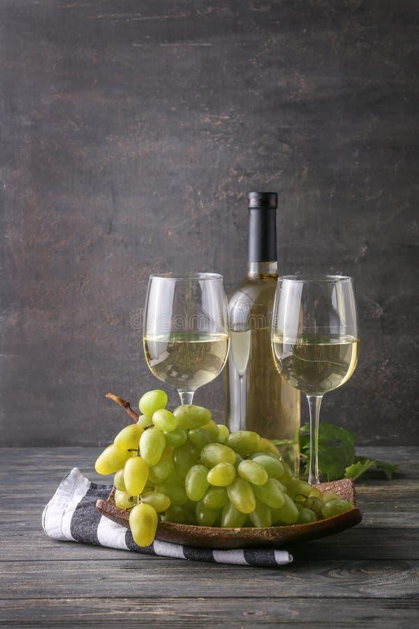 Vidrios y botella de vino blanco con las uvas maduras en la tabla de madera fotografía de archivo