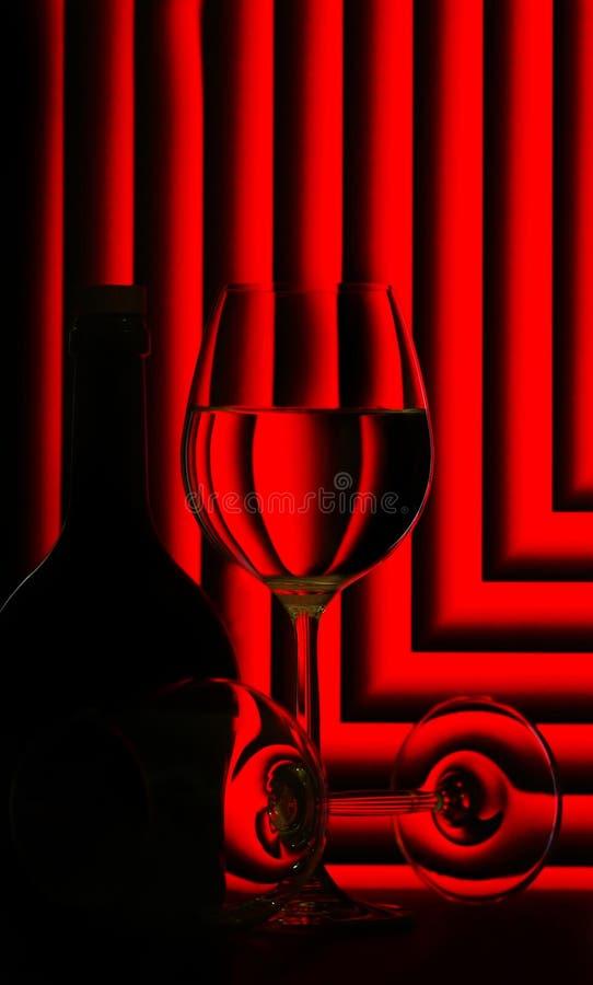 Vidrios y botella de vino en rojo foto de archivo libre de regalías