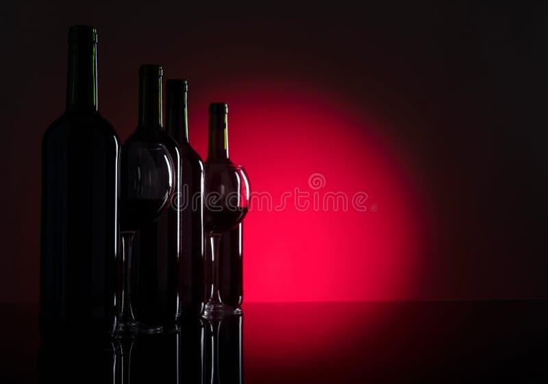 Vidrios y botellas de vino rojo fotografía de archivo libre de regalías