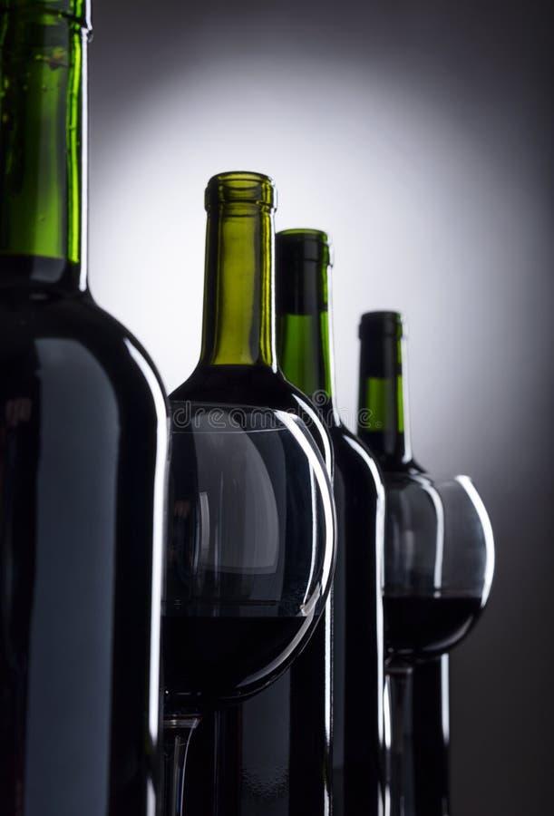 Vidrios y botellas de vino rojo imagenes de archivo