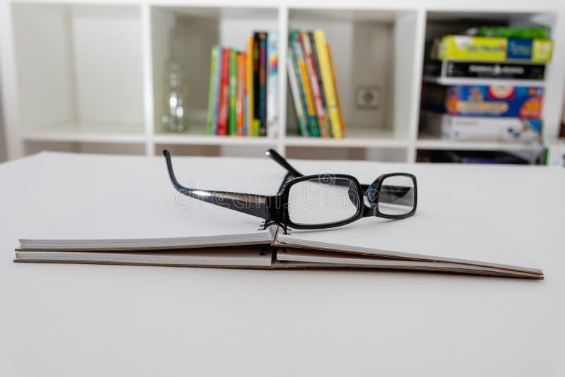 Vidrios y cuaderno en la tabla dentro Preparación para el examen fotos de archivo