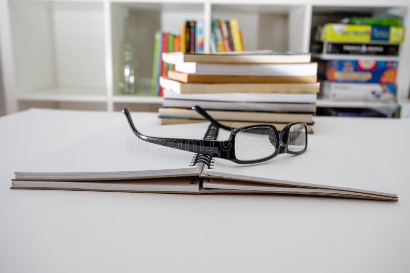 Vidrios y cuaderno en la tabla dentro Preparación para el examen fotos de archivo libres de regalías