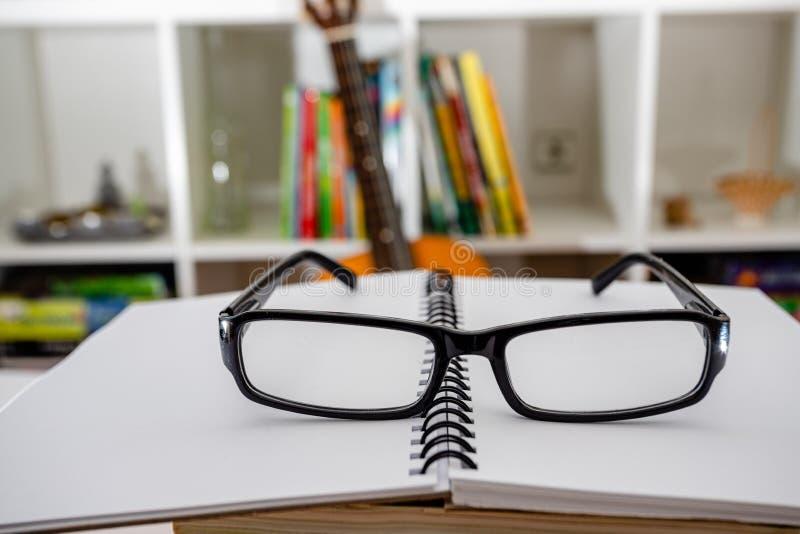 Vidrios y cuaderno en la tabla dentro Preparación para el examen imagen de archivo