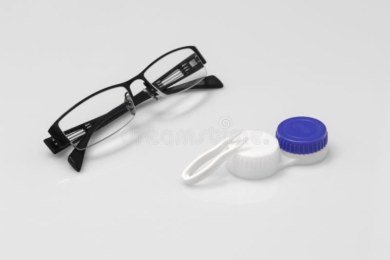 Vidrios y lentes de contacto en un fondo blanco fotos de archivo libres de regalías
