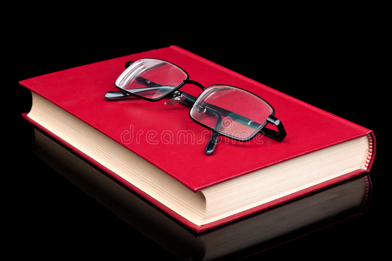 Vidrios y libro rojo imagenes de archivo