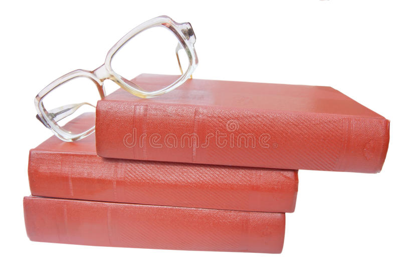 Vidrios y pila de libros marrones aislados foto de archivo