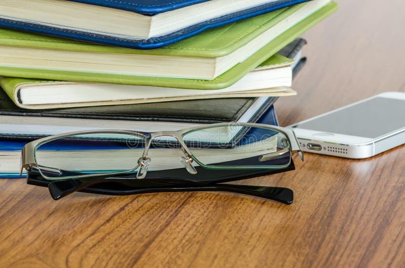 Vidrios y pila negros de libros fotografía de archivo