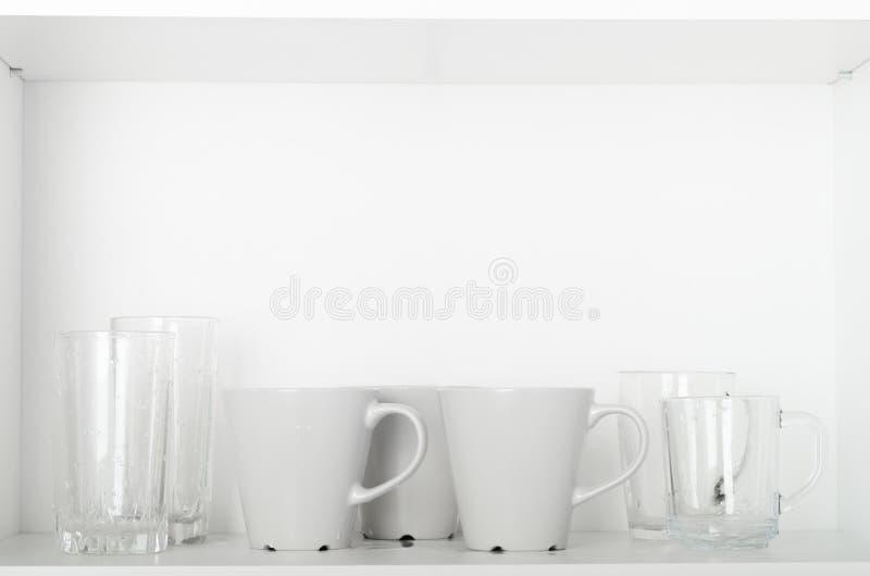 Vidrios y tazas en un estante blanco en el gabinete Platos limpios, utensilios de la cocina imagen de archivo