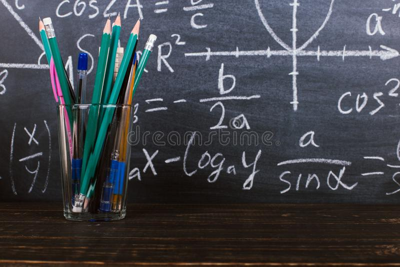 Vidrios y un vidrio con los lápices en fondo de la pizarra con fórmulas Teacher' concepto del día de s y de nuevo a escuela imagenes de archivo