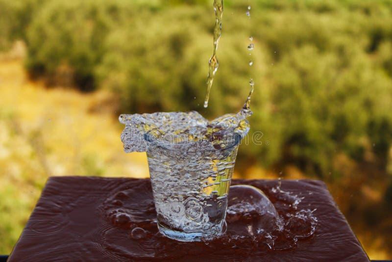 Vidro agradável da água que está sendo enchida fotografia de stock royalty free
