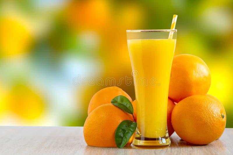 Vidro alto da posição recentemente espremida saboroso do suco de laranja em uma tabela exterior com laranjas frescas foto de stock