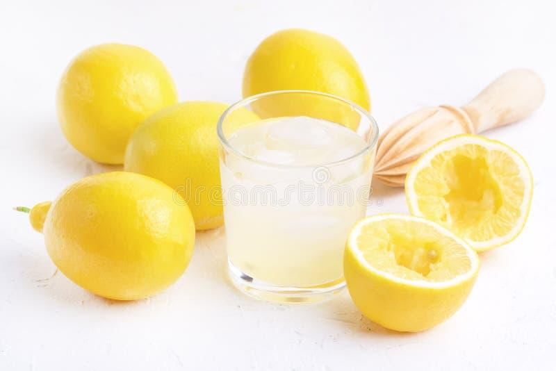 Vidro AR da limonada fresca saboroso fria com o espremedor de frutas de madeira dos limões maduros foto de stock royalty free