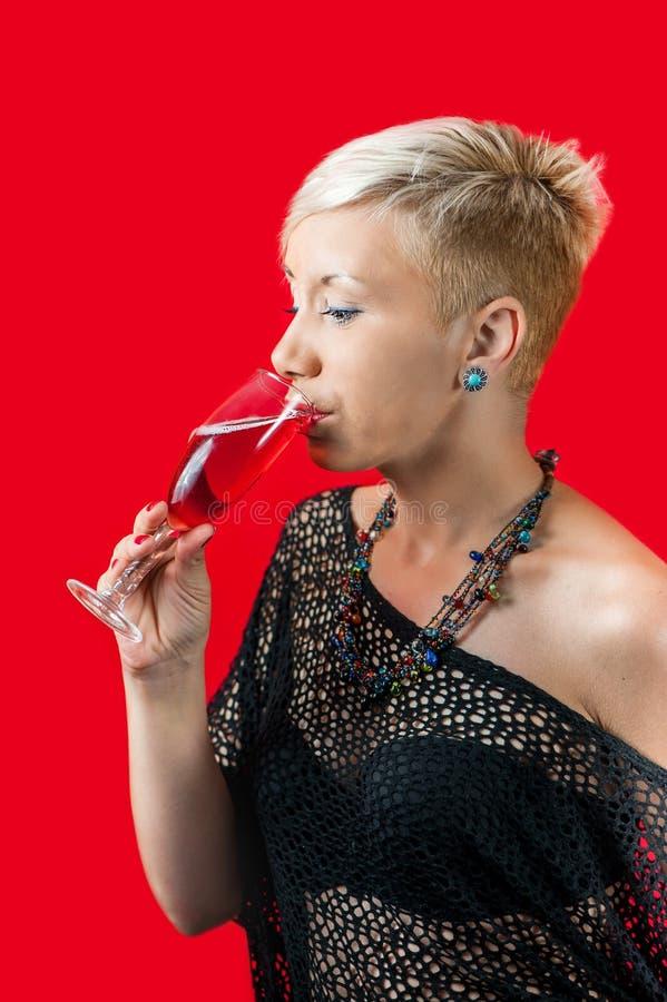 Vidro bebendo da menina loura atrativa do vinho tinto imagem de stock royalty free